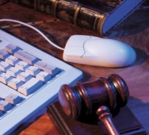 Litigation: gavel beside computer keyboard, mouse, and law book